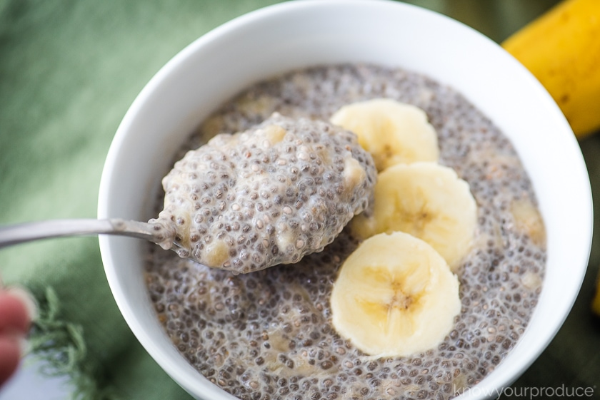 banana chia pudding in a white bowl with sliced bananas and some chia pudding on a spoon