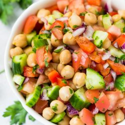 chickpea salad in a bowl with parsley on table