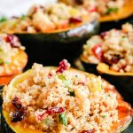 quinoa stuffed acorn squash on a baking sheet
