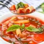 minestrone soup in a bowl and on a spoon
