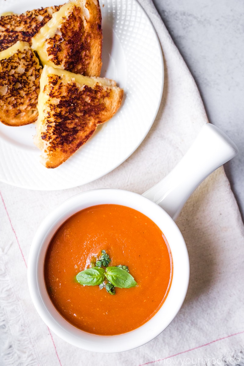 grilled cheese on a plate and tomato soup in a white bowl