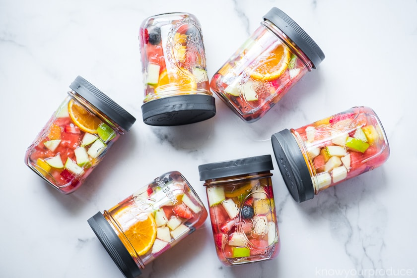 fruit infused waters in mason jars with lid on marble slab