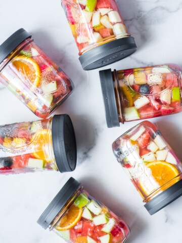 chopped fruit infused water in mason jars with plastic lids