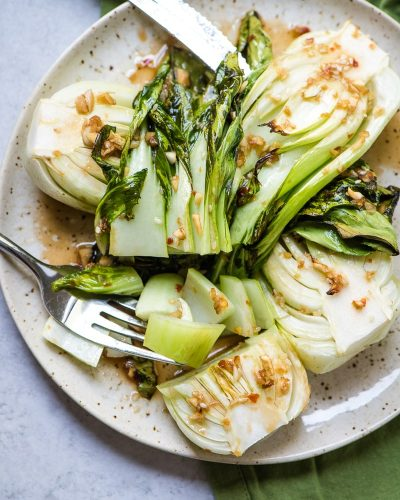 cooked boy choy on a plate cut with a fork