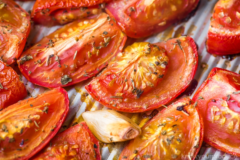 roasted tomatoes and garlic on a sheet pan