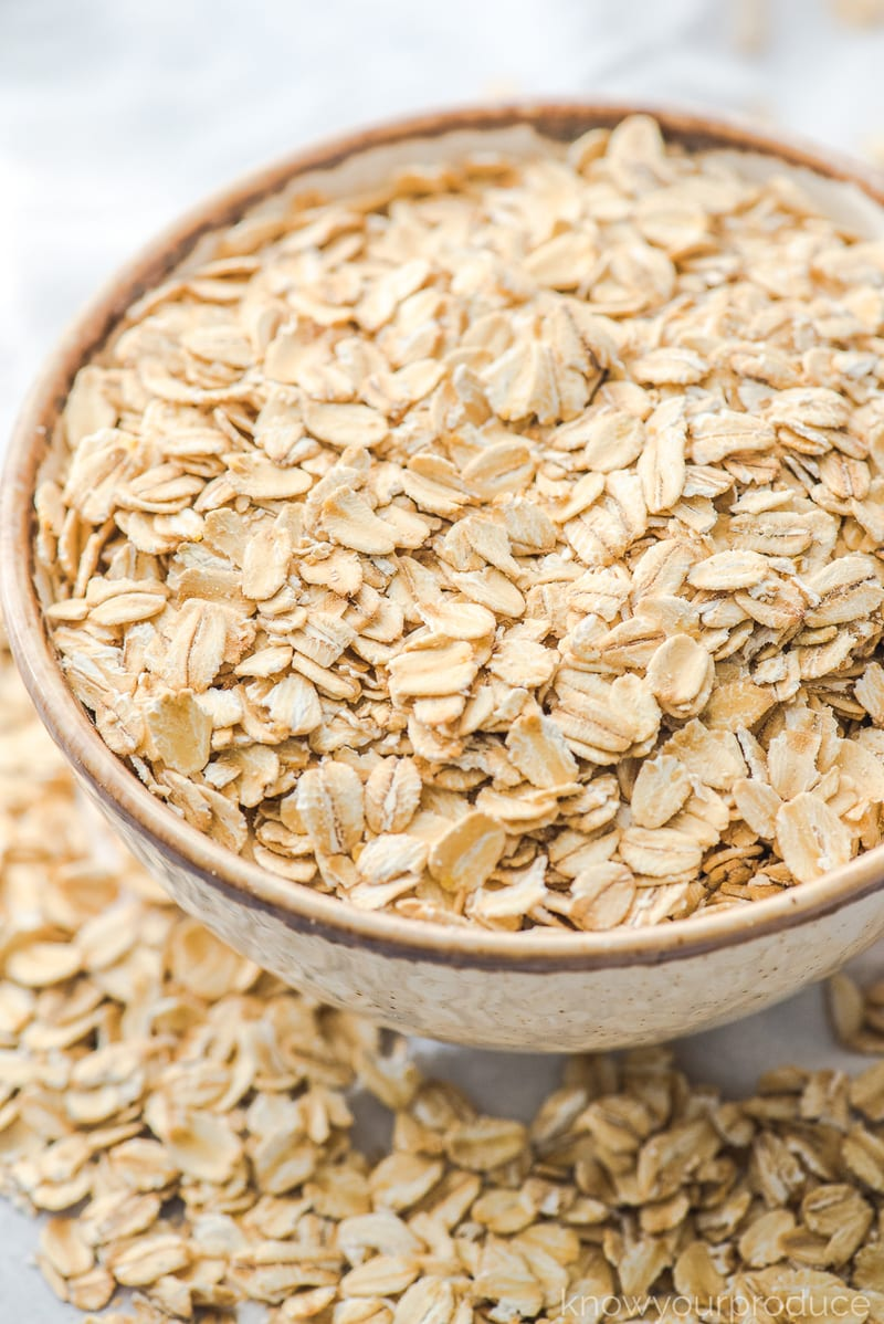 rolled oats in a bowl with oats scattered on table