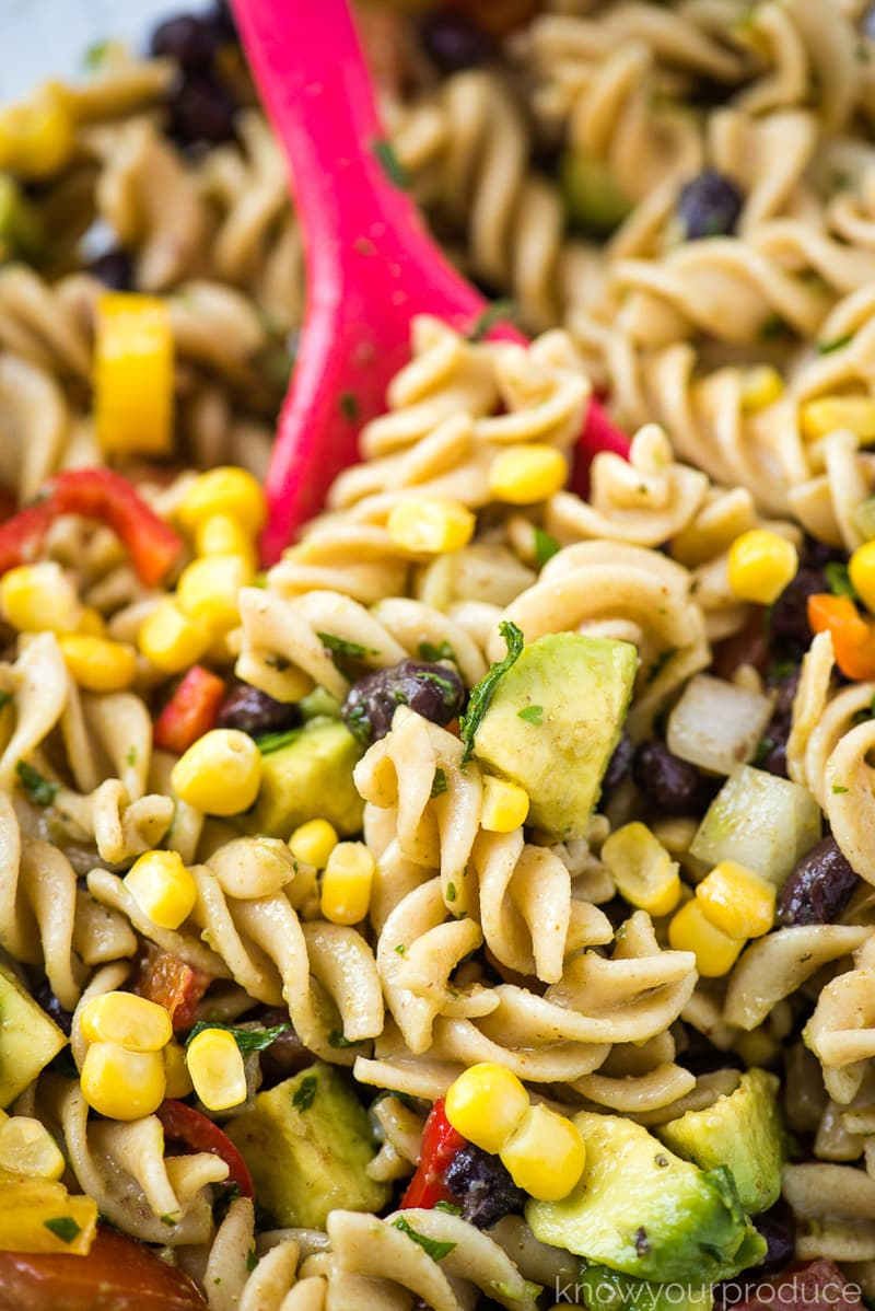 mexican pasta salad with whole wheat pasta in a bowl with pink spoon
