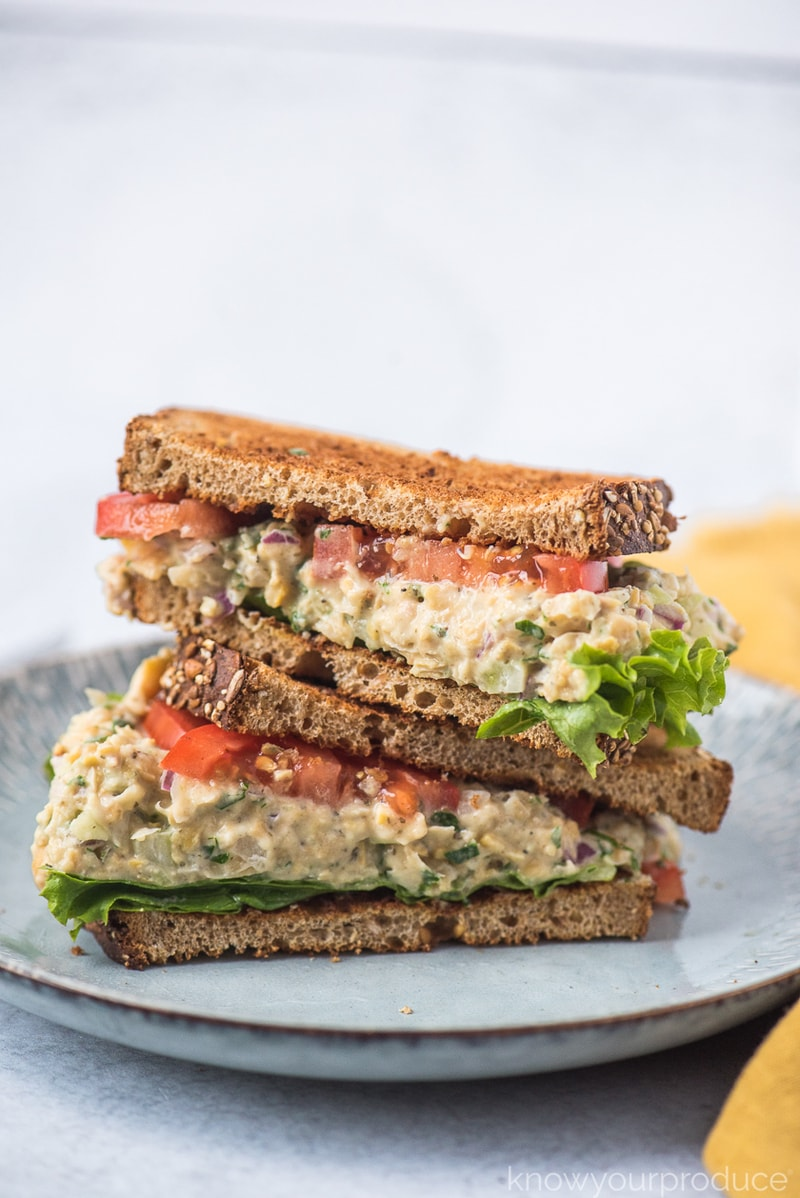 vegan tuna salad with chickpeas on wheat bread with lettuce and tomato on a light blue plate