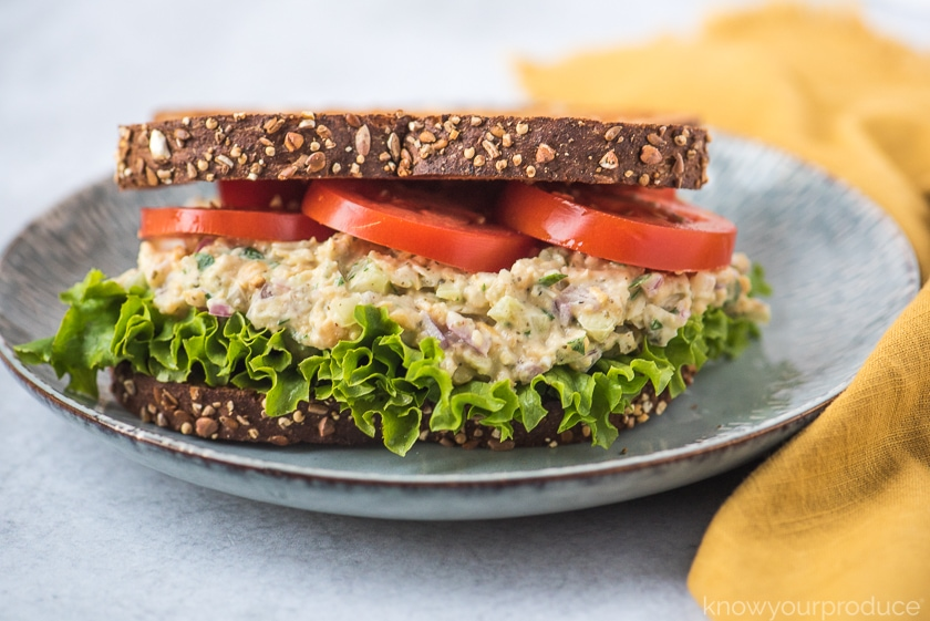 vegan tuna salad sandwich on a light blue plate with yellow napkin to the right