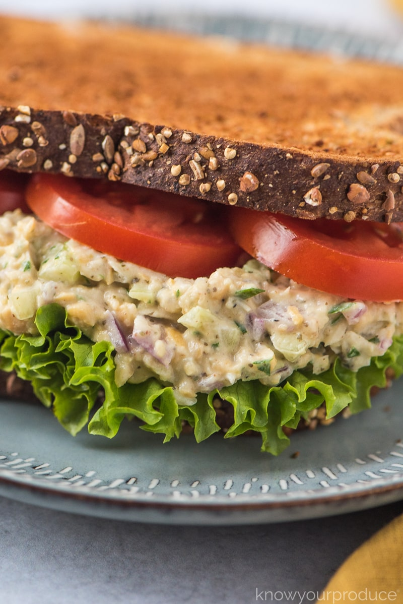 close up of vegan tuna salad on wheat bread with lettuce and tomatoes on a plate