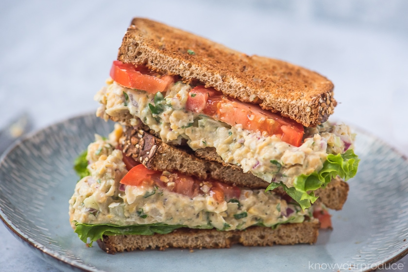 cut in half vegan tuna salad with chickpeas on wheat bread with lettuce and tomato on a light blue plate