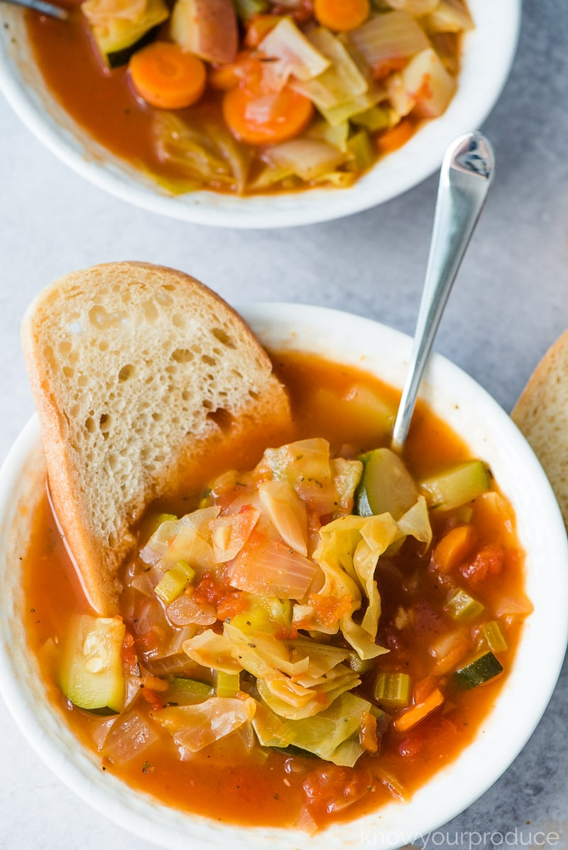 vegan cabbage soup in a bowl with bread and a spoon