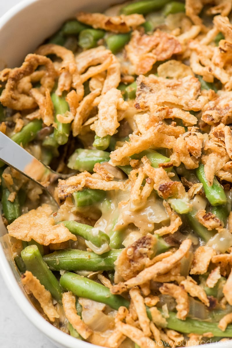 vegan green bean casserole with crispy green onions on top in white ceramic dish