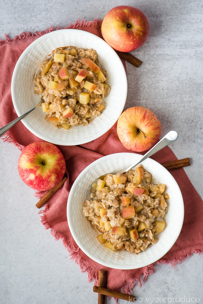 apple cinnamon oatmeal in low bowls flat lay photo with fresh apples and cinnamon sticks