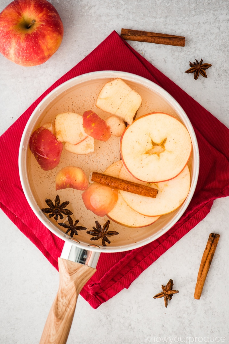 sliced apples anise cinnamon and water in a pot for simmering on a red napkin