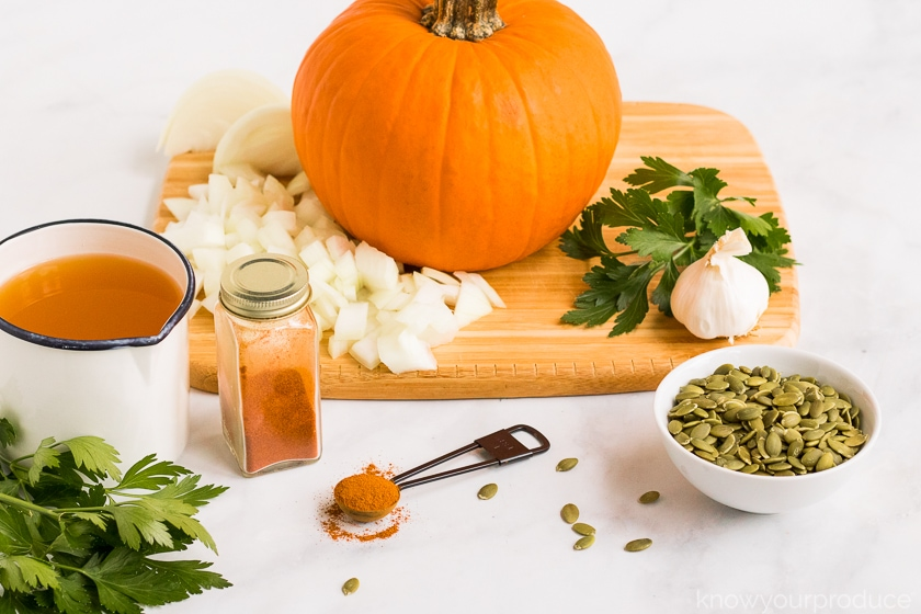 sugar pumpkin on a cutting board with chopped onions on the left herbs and garlic on the right in the lower left broth in a cup seasonings in a jar and in spoon with pumpkin seeds in a bowl to the lower right