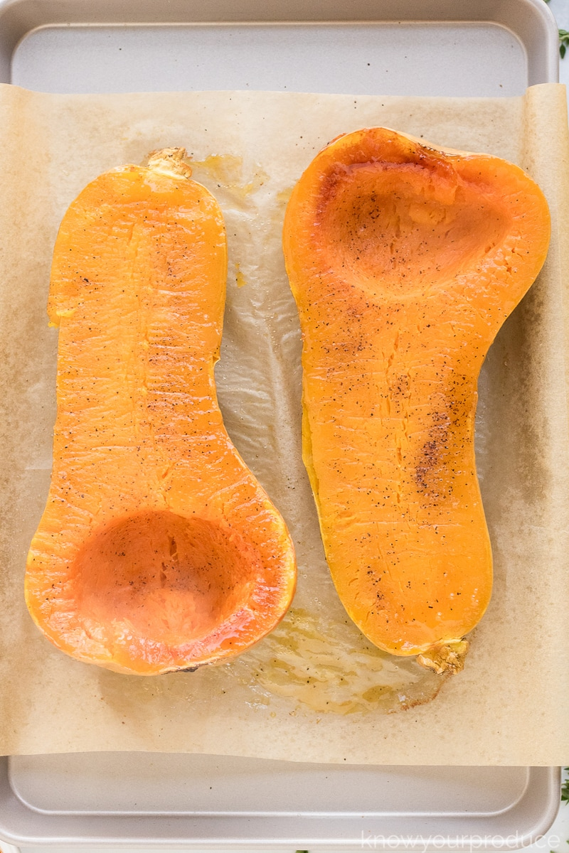 two halves of roasted butternut squash on a sheet pan with unbleached parchment paper flesh side up