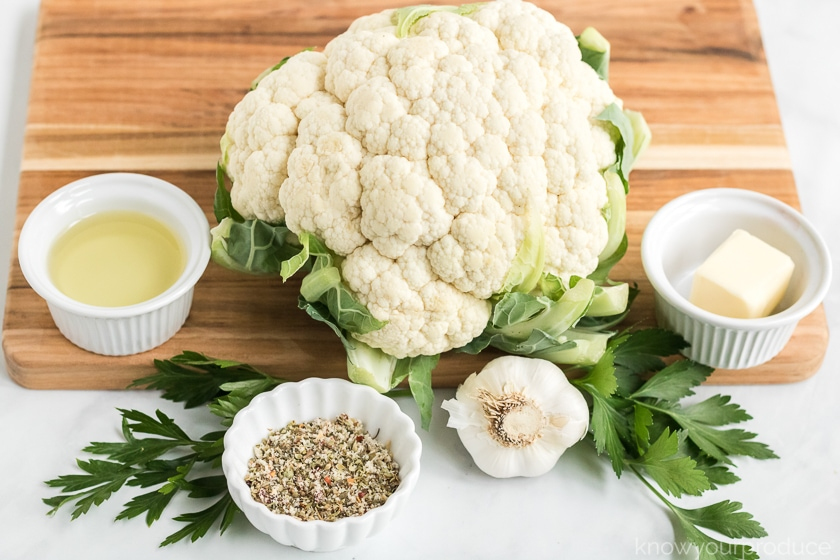 ingredients for whole roasted cauliflower on a cutting board oil butter seasonings garlic and fresh parsley