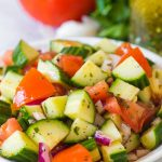 cucumber tomato salad with italian dressing in a white bowl