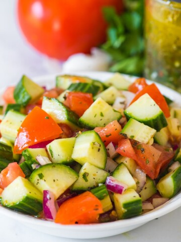 cucumber tomato salad with italian dressing in a white bowl with dressing in mason jar in background along with tomato parsley and garlic clove in background