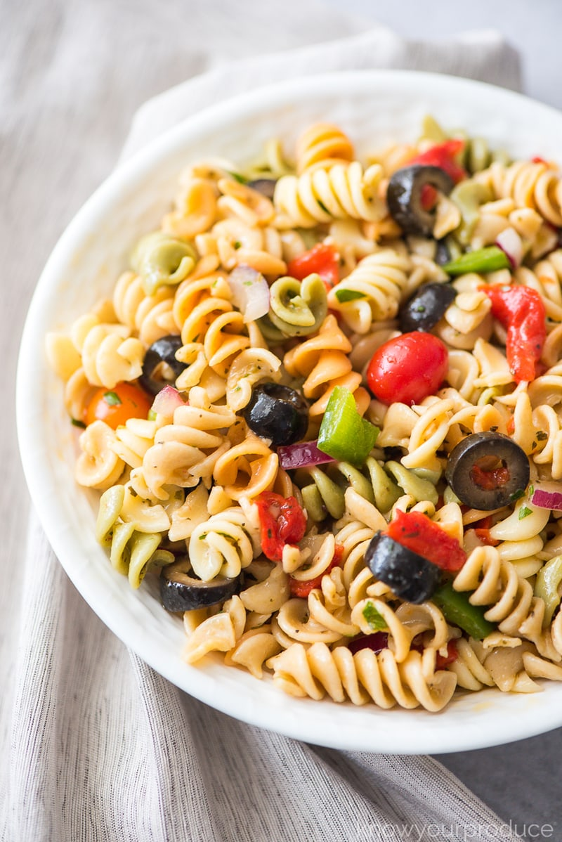 italian pasta salad with fresh vegetables and olives in a white bowl with beige napkin to the left