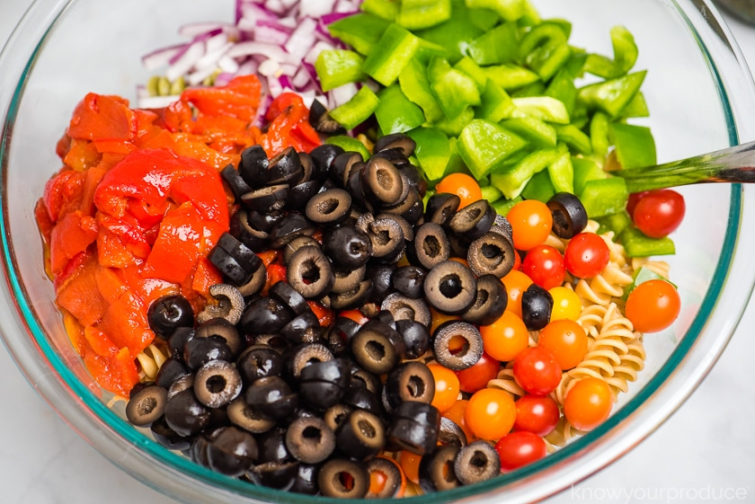 chopped vegetables olives whole petite cherry tomatoes over pasta in a large glass bowl with spoon to the right