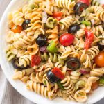 vegan pasta salad with fresh vegetables and olives in a white bowl with beige napkin to the left