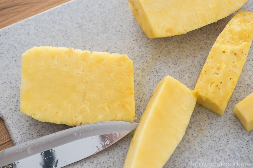 large cut pineapple on a cutting board with knife
