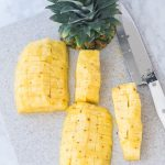how to cut pineapple on a cutting board with pineapple top and cutco chef knife to the right