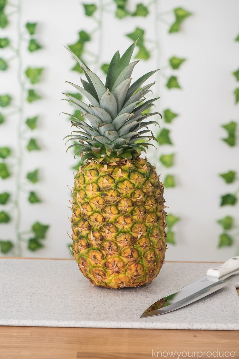 whole pineapple on a cutting board with knife and greenery in the background