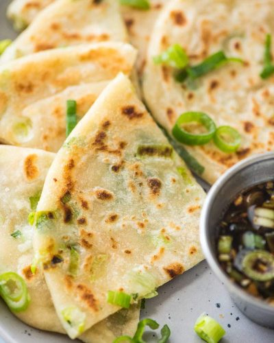 chinese scallion pancakes cut on a plate with scallion garnish and sauce to the side
