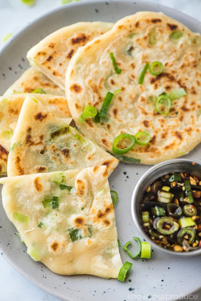 chinese scallion pancakes cut on a plate with dipping sauce on the side