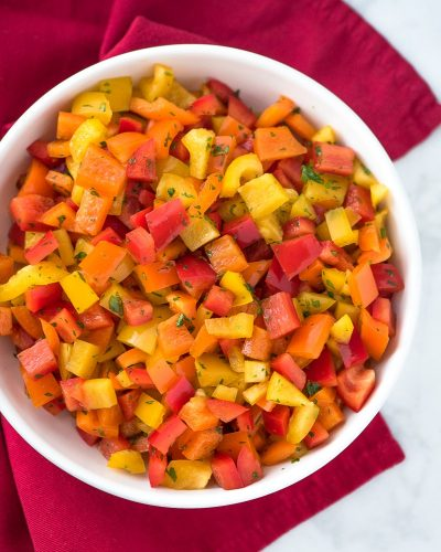 chopped bell pepper salad in a white bowl on a red napkin