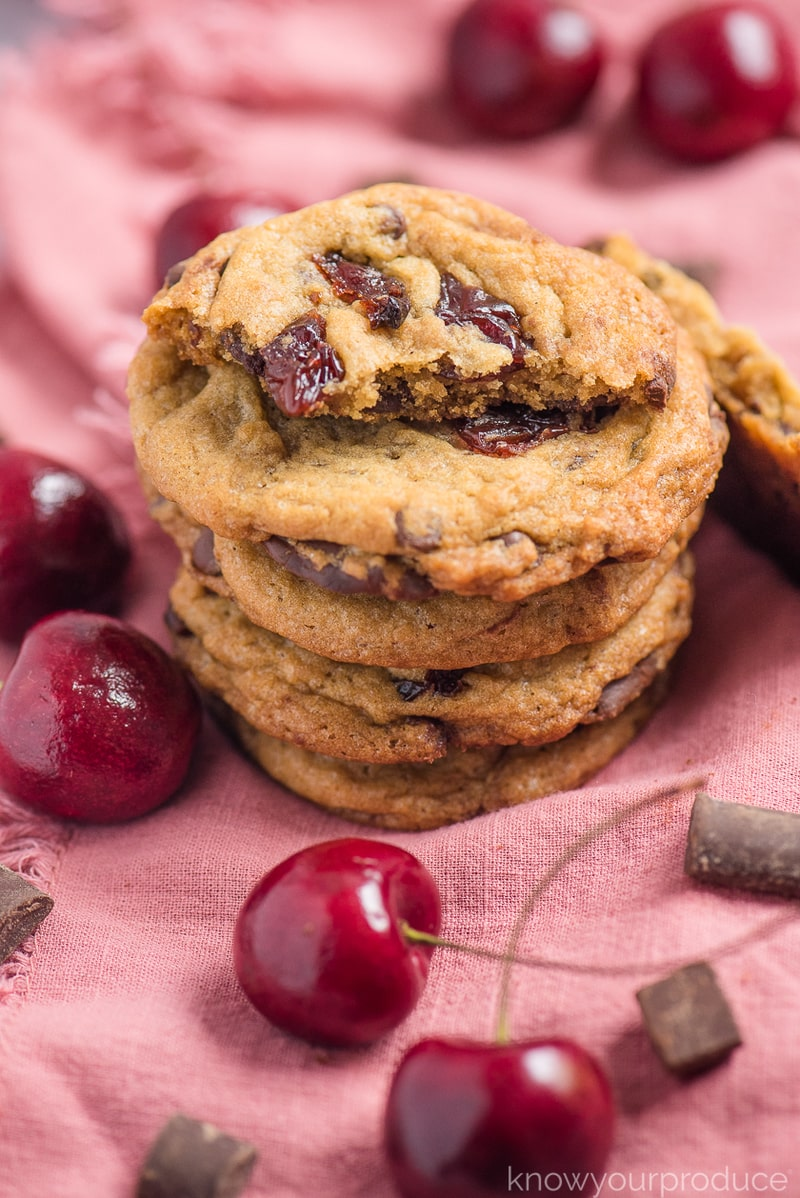 one half of a cookie and stacked cherry chocolate chip cookies on a pink napkin with chocolate and cherries scattered