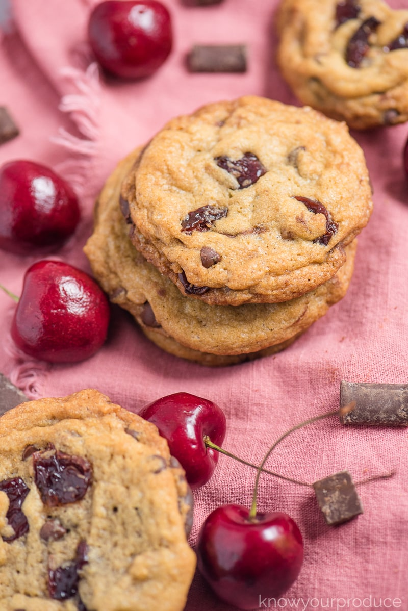 vegan cherry chocolate chip cookies on a pink cloth napkin with cherries and chocolate scattered around