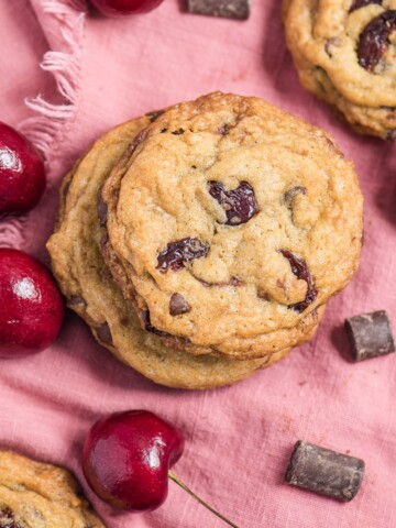 cherry chocolate chip cookies on a pink napkin with chocolate and cherries scattered