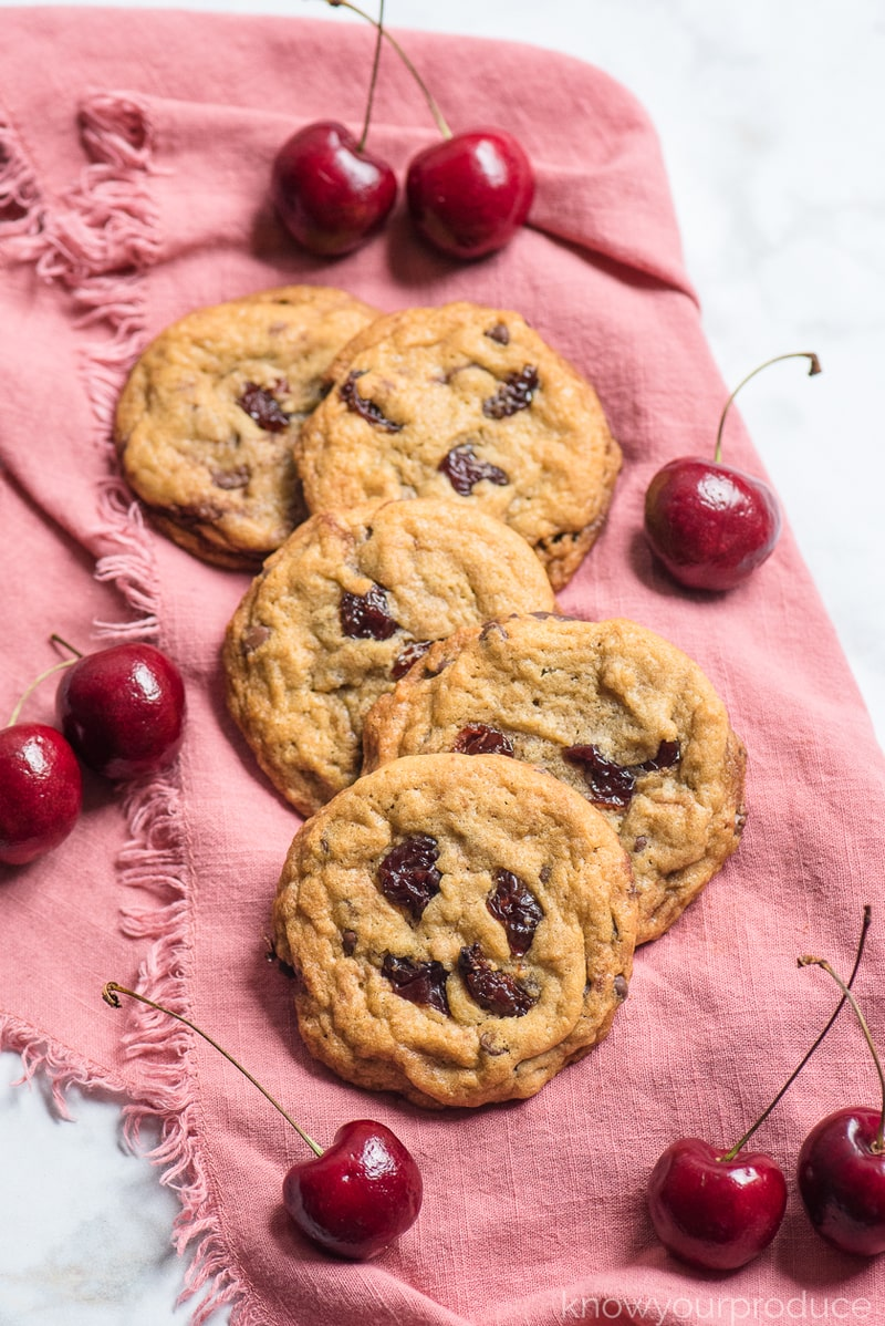 cookies on a pink napkin with cherries scattered