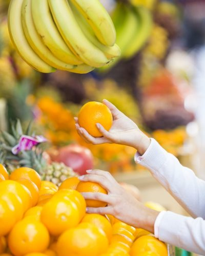 hand holding oranges with a bin of oranges and bananas hanging in produce section
