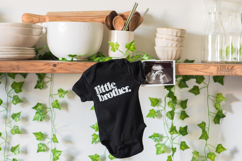 wooden shelf with bowls and cups and green vines behind it onesie saying little brother hanging and baby ultrasound picture pinned to wooden shelf