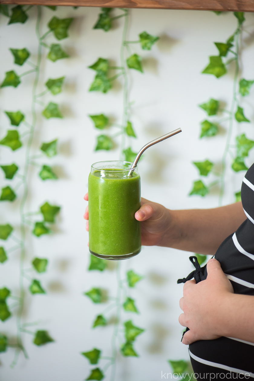 pregnancy smoothie in a glass with a stainless steel straw being held by a hand and hand holding a pregnant belly with greenery in the background