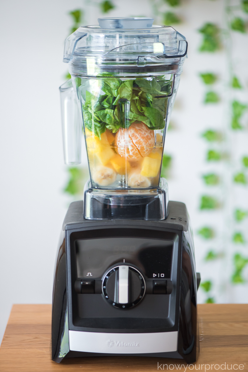 vitamix blender with spinach and frozen fruit inside ready to blend