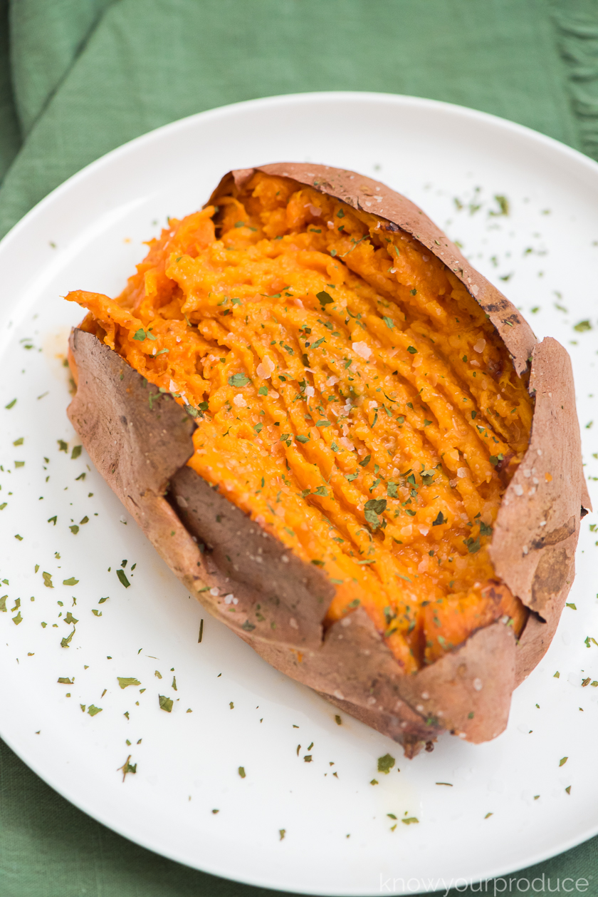 fork mashed air fryer sweet potato seasoned with kosher salt and parsley on a white plate and green napkin