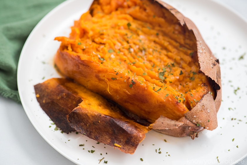 skin peeling off sweet potato on a white plate with green napkin on the upper left corner
