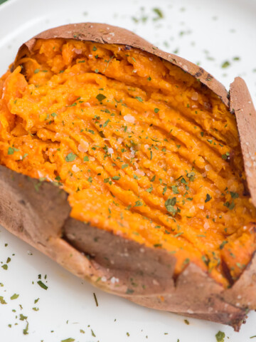 fork mashed air fryer sweet potato seasoned with kosher salt and parsley on a white plate