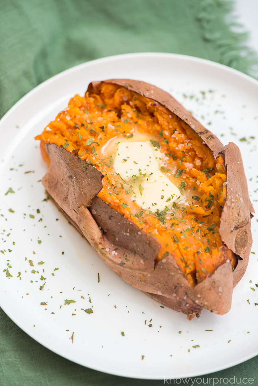 fork mashed air fryer sweet potato seasoned with kosher salt and parsley and two tabs of butter on a white plate and green napkin