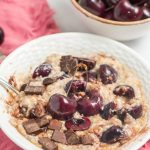 oatmeal with fresh cherries and chocolate chunks with spoon in a white low bowl on a pink napkin with cherries in a small ceramic bowl in the back right