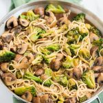 broccoli mushroom stir fry with lo mein in a stainless steal pan on a green napkin