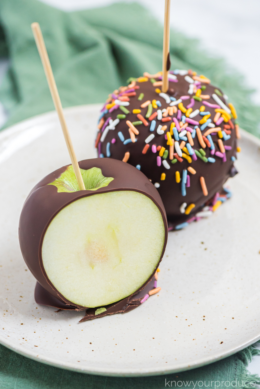 sliced chocolate covered apple on a plate with sprinkle covered apple behind it on a green nappkin