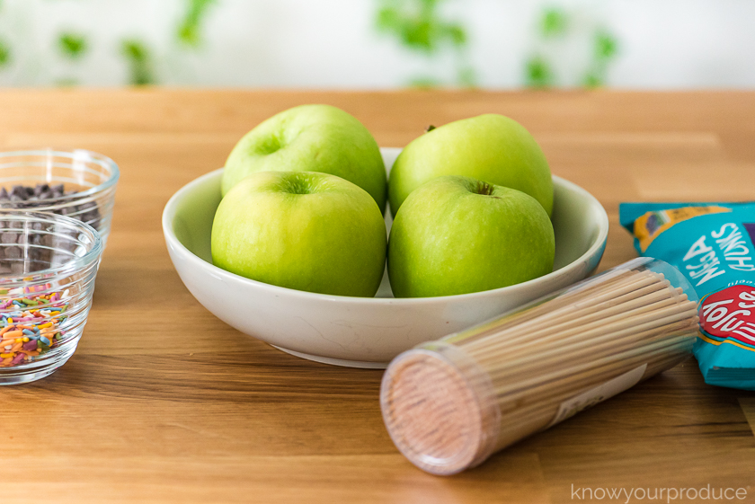 granny smith apples in a bowl with screwers and chocolate chips to the side and sprinkles and chocolate chips to the left in glass bowls on a table