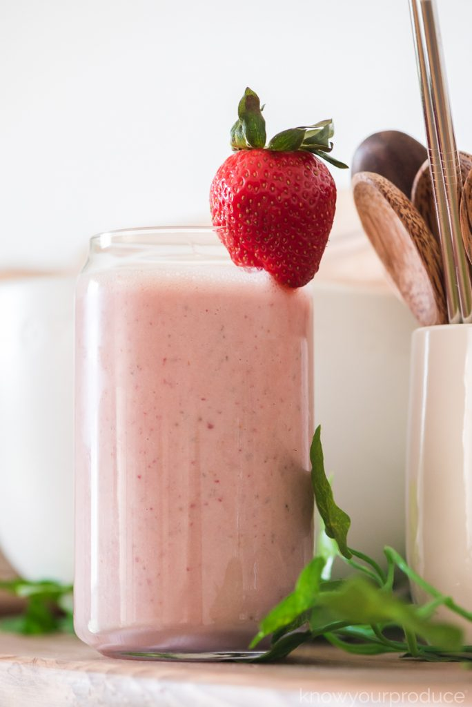fresh strawberry peanut butter banana smoothie in a glass with strawberry on top on a wooden shelf with small bowls and cup with wooden spoons in background